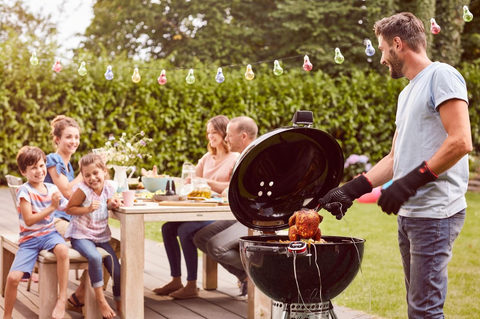 Rodzina zdziećmi, siedząca przy ogrodowym stole przy grillu.