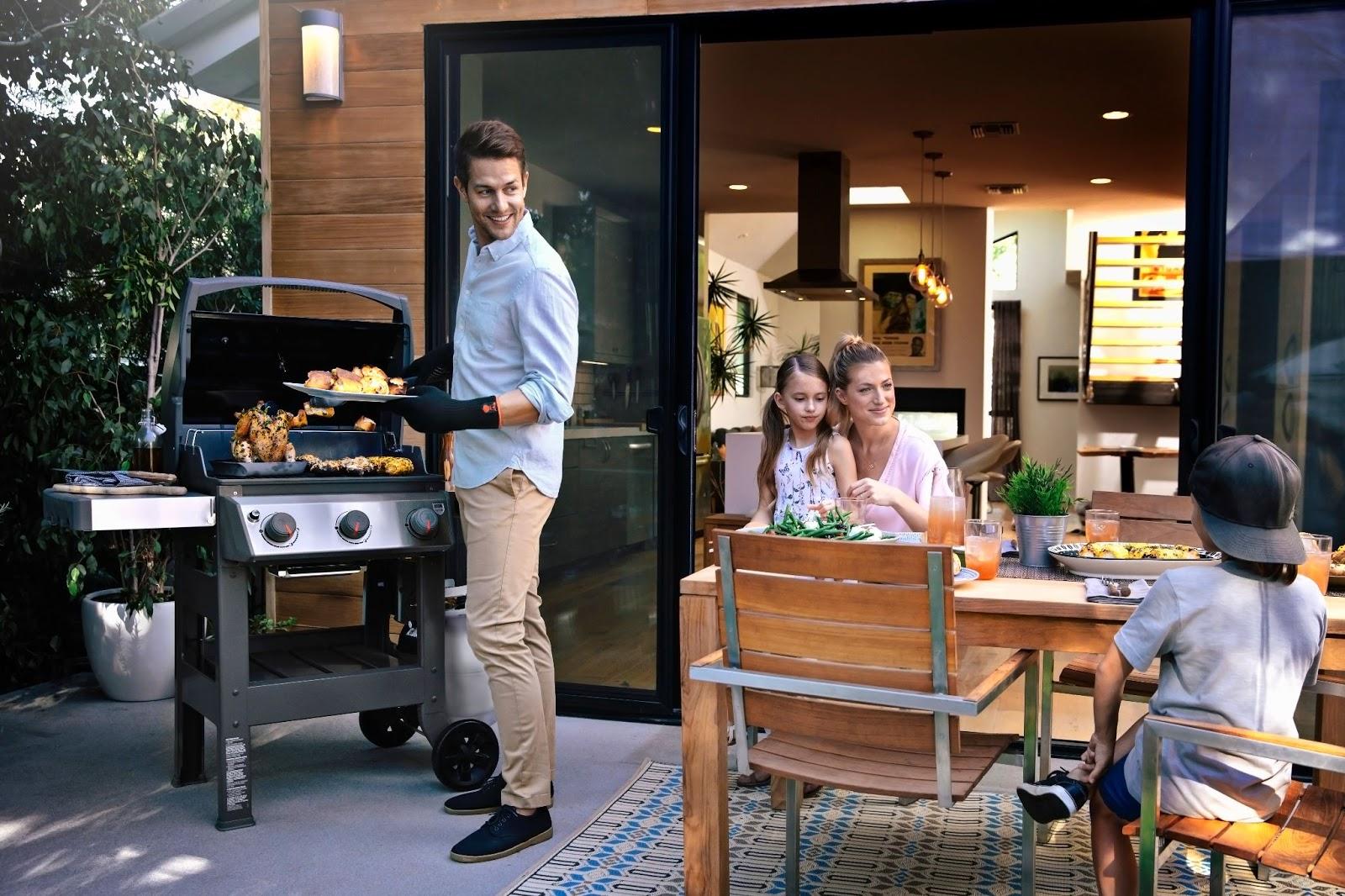 Wesoła rodzina grillująca nadomowym tarasie.